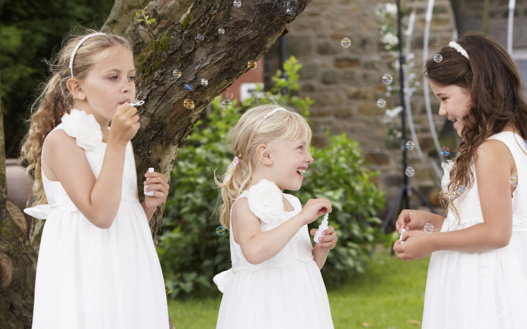 Three little girls blowing bubbles at a garden wedding